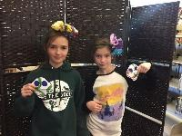 Two children holding crafts they made at a library program