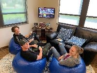 Teens sitting on bean bag chairs playing a video game at the library