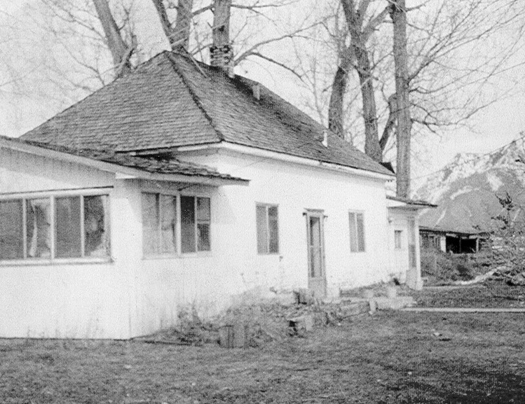 A black and white image of a house near trees